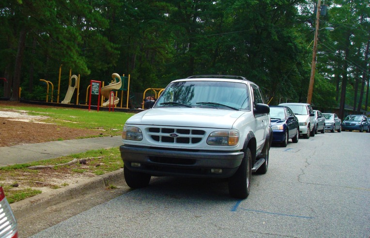 cars lined up in front of the playground